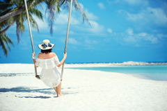 Beautiful woman swinging on a Tropical beach, Koh Phangan island. Thailand. Stock Photography