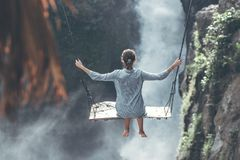 Beautiful woman swings near waterfall in the jungle of Bali island, Indonesia. Beautiful woman swings near waterfall in the jungle of Bali island royalty free stock image
