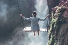 Beautiful woman swings near waterfall in the jungle of Bali island, Indonesia. Beautiful woman swings near waterfall in the jungle of Bali island Royalty Free Stock Photos
