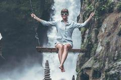 Beautiful woman swings near waterfall in the jungle of Bali island, Indonesia. Beautiful woman swings near waterfall in the jungle of Bali island Stock Images