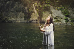 Beautiful woman with a sword in a stream Stock Photo