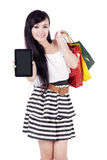 Beautiful woman with tablet. Beautiful asian woman showing empty screen of computer tablet while carrying shopping bags Stock Images