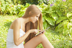 Beautiful Woman With Tablet Computer In Garden Stock Photo