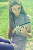 Beautiful Woman With Tablet Computer In Park Stock Photography