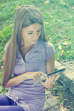 Beautiful Woman With Tablet Computer In Park Royalty Free Stock Photography