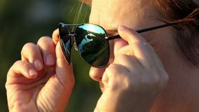 Beautiful woman takes off her sunglasses outdoors at sunset. An attractive middle-aged woman takes off her modern sunglasses and smiles slightly at a splendid stock footage