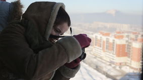 Beautiful woman takes photos of the winter city from a height. Her camera is compact. She smiles, she has dark hair, brown coat, green scarf and red gloves. At stock video