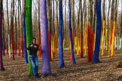 The beautiful woman takes pictures and enjoys a forest painted i. N different colors Royalty Free Stock Photos
