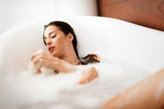 Beautiful woman taking care of her body in bathtub Royalty Free Stock Photos
