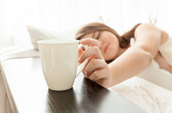 Beautiful woman taking cup of coffee at bed Royalty Free Stock Photos
