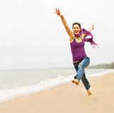 Beautiful woman taking a great leap. A beautiful energetic young woman taking a great leap on the beach Stock Photography