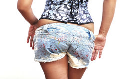 Beautiful woman taking off her denim shorts Royalty Free Stock Photos