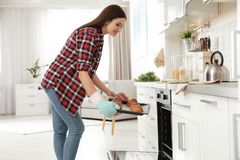 Beautiful woman taking out tray of baked buns from oven royalty free stock images