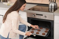 Beautiful woman taking out tray of baked cookies from ovenк stock photo
