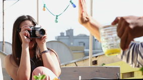 Beautiful woman taking photos of her friends with old fashioned camera. Beautiful brunette woman taking photos of her friends with old fashioned camera stock video footage