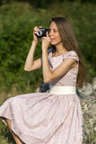 Beautiful woman is taking picture with old fashioned camera, outdoors. Royalty Free Stock Photo
