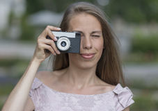 Beautiful woman is taking picture with old fashioned camera, outdoors. Royalty Free Stock Images