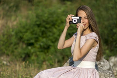 Beautiful woman is taking picture with old fashioned camera, outdoors. Stock photo Royalty Free Stock Images