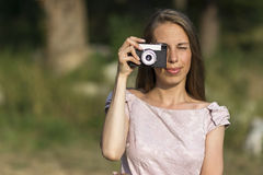 Beautiful woman is taking picture with old fashioned camera, outdoors. Stock photo Stock Images