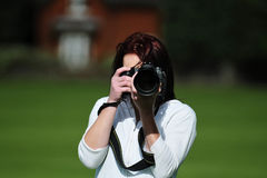 Beautiful Woman Taking Pictures. Beautiful young woman taking photos with professional camera in nature Royalty Free Stock Images