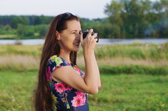 Beautiful woman taking pictures of sunset Stock Photo
