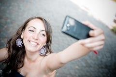 Beautiful woman taking self-portrait Stock Images