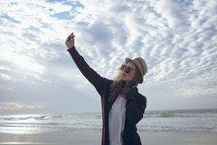 Beautiful woman taking selfie at beach. Side view of pretty young Caucasian woman with hat and sunglasses taking selfie with her mobile phone standing at beach stock photos