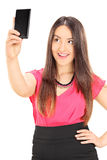 Beautiful woman taking a selfie with cell phone Stock Images