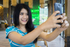 Beautiful woman taking selfie photo in cafe Stock Photography