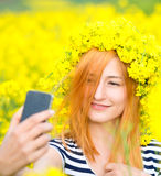 Beautiful woman taking selfie picture of herself in yellow field with natural background Stock Photo
