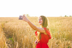 Beautiful woman taking selfie picture of herself in yellow field with nature background. Close up portrait of a young Royalty Free Stock Photography