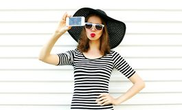 Beautiful woman taking selfie picture by phone blowing red lips sending sweet air kiss on white wall background. Female model wearing black summer straw hat stock image