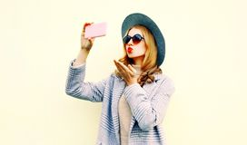 Beautiful woman taking selfie picture by smartphone blowing red lips sending sweet air kiss in pink coat jacket, round hat royalty free stock images