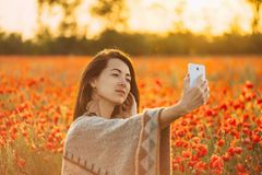 Beautiful woman taking selfie in poppies meadow. Smiling beautiful young woman boho stylish taking selfie portrait with smartphone in red poppies flowers meadow stock photo