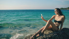 Beautiful woman taking selfie using phone on beach smiling and enjoying traveling lifestyle on vacation. Beautiful woman taking selfie using phone on beach stock video footage