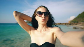 Beautiful woman taking selfie using phone on beach smiling and enjoying traveling lifestyle on vacation. Beautiful woman taking selfie using phone on beach stock video