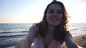 Beautiful woman taking selfie using phone on beach at sunset smiling and spinning enjoying nature and lifestyle. On vacation, slow motion stock video