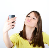 Beautiful woman taking selfies against white background Royalty Free Stock Photos