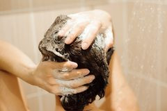 Beautiful woman taking a shower. Washing hair with Shampoo.  stock photography
