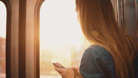 Beautiful woman taking a subway in Chicago, USA. Attractive female using smartphone while train is moving on sunset. stock footage