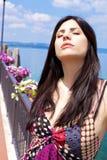 Beautiful woman taking sun on lake with flowers Royalty Free Stock Photo