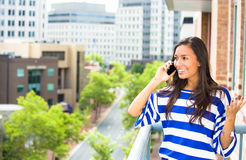 Beautiful woman talking on a cell phone relaxed on a balcony of her apartment on a city background. A portrait of a beautiful woman talking on a cell phone Royalty Free Stock Photos