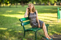 Beautiful  woman talking on cell phone while sitting on the bench in summer Park. Stock Image