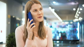 Beautiful woman talking on a cellphone in a mall. Shopping consumerism concept. stock footage
