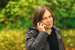 Beautiful woman talking on mobile phone in autumn park Royalty Free Stock Photography