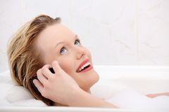 Beautiful woman talking by mobile phone in bath. Stock Photos