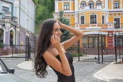 Beautiful woman talking on a mobile phone on a city street. Royalty Free Stock Images