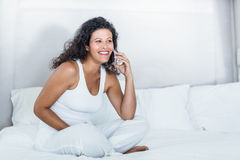 Beautiful woman talking on mobile phone while sitting on bed Stock Images