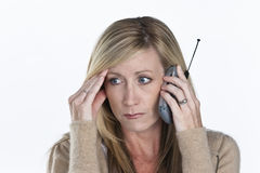 Beautiful Woman Talking on Phone. A distraught mature blond female talking on a cellular phone Stock Photography