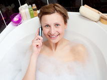 Beautiful woman talking on phone in a bubble bath Stock Photo